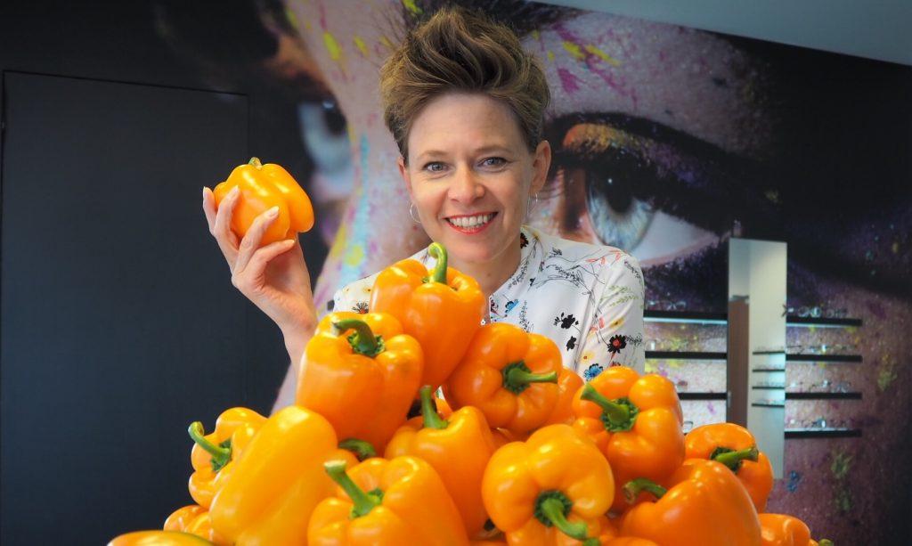 Brillenmeisje met oranje paprika's die goed zijn voor je ogen